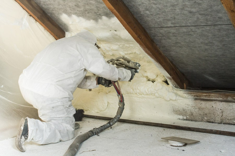 Worker wearing white protective suit spraying insulation for a commercial building